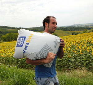 Man carrying a bag of fertiliser keeping head up and back straight to avoid injury